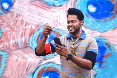 Young indian man holding mobile phone inserting earphone plug at device - Happy asian guy using smartphone headset outdoor in casual sport look - Concept of modern communication technology - Image