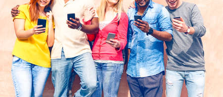 Teenagers texting mobile phone messages row on pink background - Multiracial friends holding smartphone smiling - Multicultural teens generation using cellphone - Modern communication concept - Image