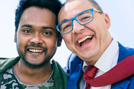 Happy interracial couple of friends male taking selfie laughing - Indian and caucasian men smiling at camera in positive attitude - Concept of friendship between different culture and race - Image