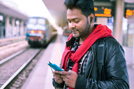 Indian man at train station using mobile phone with earphone - Young asian guy waiting public transport standing on platform holding cellphone looking down - Concept of technology and travel - Image
