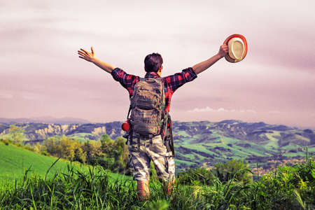 Young man open arms on top of mountain - Rear view of hiker raising hands to cloudy sky standing on green uplands at sunset lights - Travel  concept of freedom and success -  Vintage filter look image