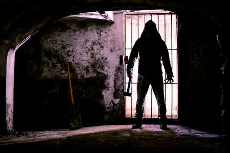 Scary dark man holding hammer inside dungeon - Silhouette of serial killer standing in creepy prison with threatening attitude - Concept of madness and murder - Backlight image with enhanced contrast