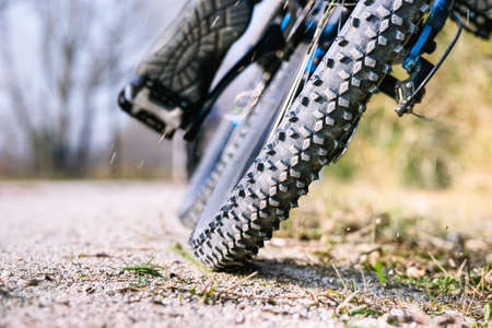 Mountain bike tire low angle closeup on trail - Man cycling mtb outdoor back view of wheel on  gravel ground - Concept of sport bicycle activity and tyre performance - Image