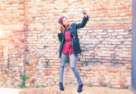 Trendy fashion girl taking selfie on old bricks wall background autumn season clothing - Young woman holding phone looking at mobile camera sending kisses - Concept of social media teenage trends Stock fotó