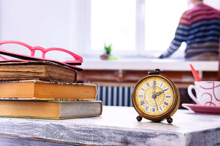 Old alarm clock and vintage books on wooden table with man looking out the window on background - The subjectivity of time - Concept of self-isolation , stress and  anxiety staying at home - Image