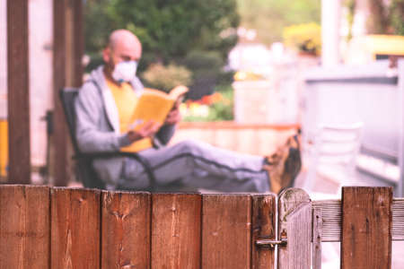 Man with face mask reading book in courtyard main focus on the fence - Concept of social isolation spending time staying at home and restrictions due to the covid-19 pandemic - Copy space Image Stock fotó