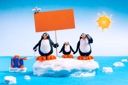 Penguin family on floating ice holding empty sign to protest global warming - Plasticine animals in funny dramatic scene of climate changes - Environmental concept of   temperature increase - Image Stock fotó