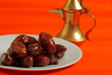 Dates and golden arabic teapot in the background photo