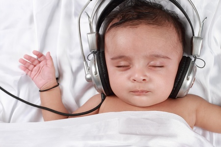 music education: 2 Month old baby listening to music with headphones