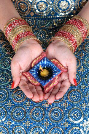 bangles hand: Diwali Celebration Diya on a Female Hand