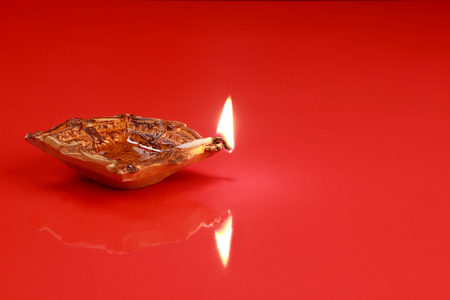 holiday tradition: Handmade Diwali Clay Lamp on Red Color Background Stock Photo