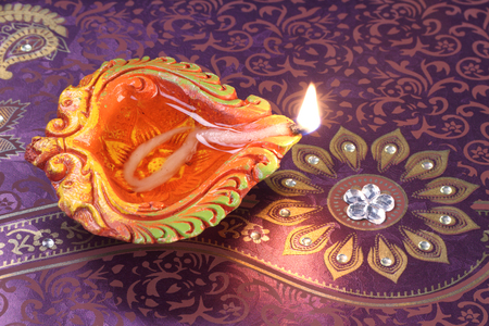 holiday tradition: Handmade Diwali Clay Lamp on Floral Background Stock Photo