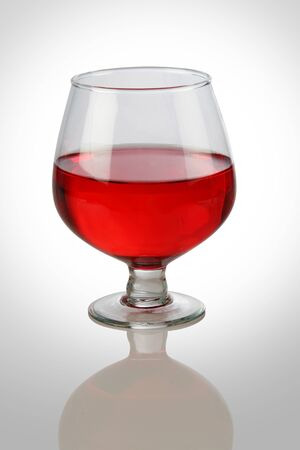 glass of red wine: Red Wine Glass on White Reflective Background
