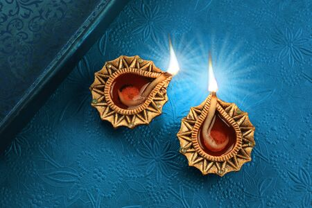 Beautiful Golden Diwali Diya Lamp Lights on Blue Background Stok Fotoğraf