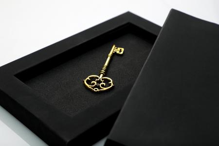 Llave dorada antigua en caja negra Foto de archivo