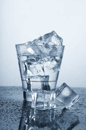 Chilled Glass of Water with Ice Cube and Water Drops