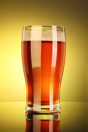 Full Beer Glass with Yellow Background Standard-Bild - 119903624