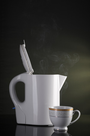 Tea Cup and Electric Kettle with Steam Imagens