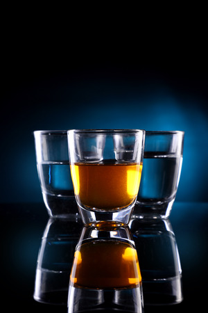 Three Shot glasses with alcohol drinks Imagens
