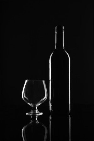 Red Wine Bottle and Glass on Black Background Imagens