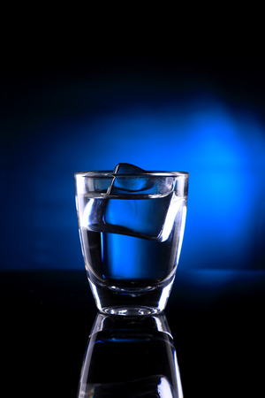 Shot Glass with an Ice Cube on Blue background