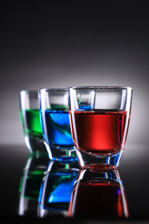 Three Colorful Shot Glasses on Grey Background with Reflections Standard-Bild - 119903590