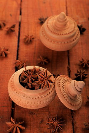 Indian Spice Star Anise in a Handmade Pottery Container on Wooden Background