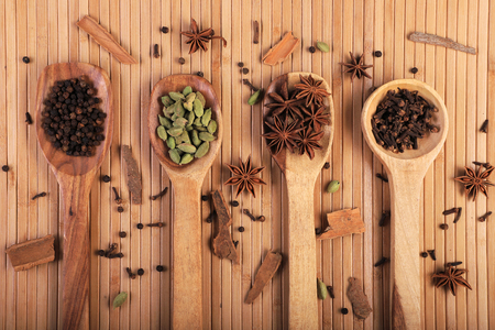 Indian Spices Black Pepper, Cardamom, Star Anise and Cloves in Wooden Spoons  Spatula