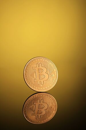 Golden Bitcoin Money Currency on Gold Background with Reflections