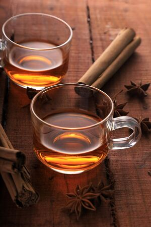 Herbal Tea with Star Anise and Cinnamon in a Cup on Wooden Table