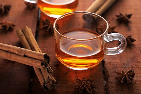 Healthy Herbal Tea with Star Anise and Cinnamon in a Cup on Wooden Table Фото со стока