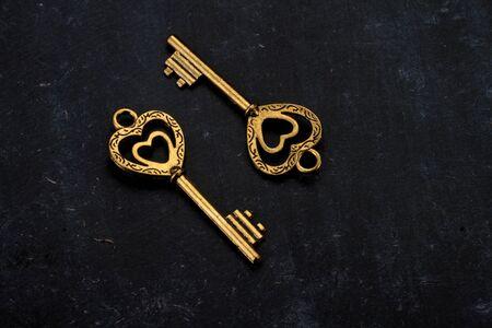 Unlock My Heart - Two Heart Shaped Golden Vintage Keys on Black Background Фото со стока