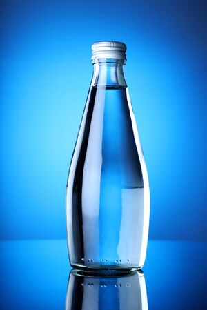 Clean and Pure Mineral Drinking Water Bottle with Blue Background Фото со стока