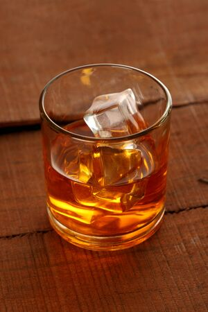 Chilled Whisky Glass with Ice Cubes on Wooden Table