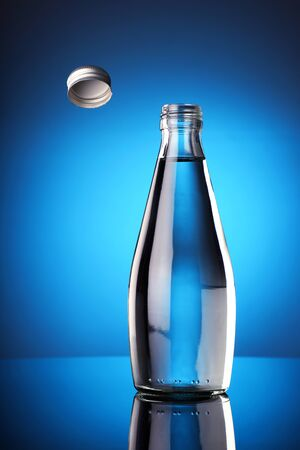 The Bottle Cap Challenge Concept - Fresh water in a bottle with open cap flying