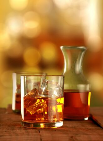 Chilled Whisky Glass with Ice Cubes on Blurred Background Фото со стока