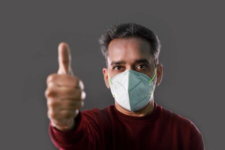 Indian Man wearing a N95 mask and showing thumbs up for protection against virus, dust, pollution and smog Stock Photo