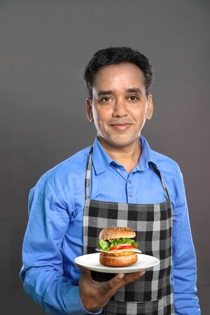 Indian Male Chef with a Burger in Hand on Grey Background Standard-Bild