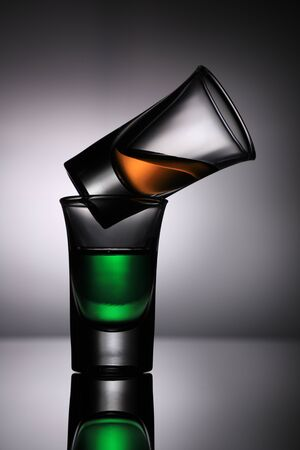 Two Drink Shot Glasses - Green and Orange on grey background Standard-Bild