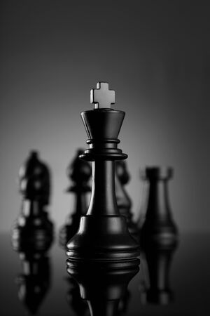 Leadership Chess King with pieces on dark background