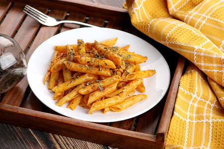Food - Tasty Penne Pasta Plate with a Fork on Wooden Tray Standard-Bild