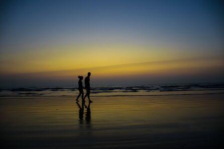 Silhouette photograph of a couple walking on Nagaon beach in Maharashtra, India at twilight Imagens