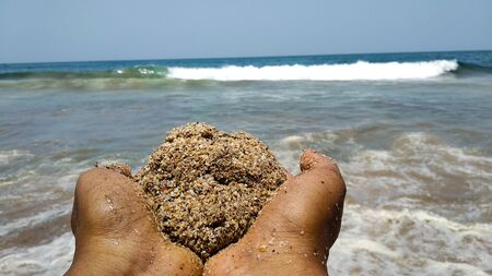 Photo of hands with a ball of sand at a beach in India