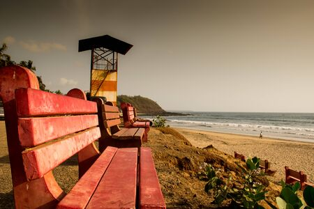Red colored benches facing the sea at Velneshwar beach situated in Maharashtra state of India. The photograph is clicked on an evening.