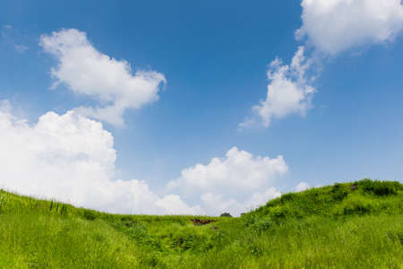 Photograph of lush green hill landscape with clouds as background in rural Satara region of Maharashtra, India