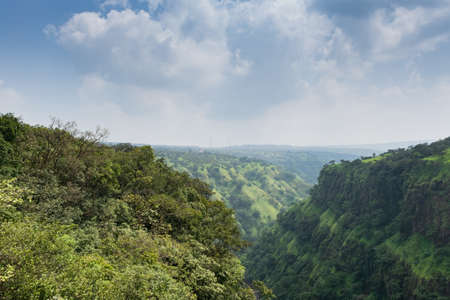 Panoramic view of lush green valley covered in trees. The photograph is clicked on a foggy winter day at Satara, Maharashtra, India.