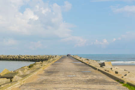 Panoramic view of a beautiful curvy footpath going towards a lighthouse at Scheveningen Beach located on the coast of North Sea in The Hague, Netherlands. Photograph clicked on a bright sunny Summer day.