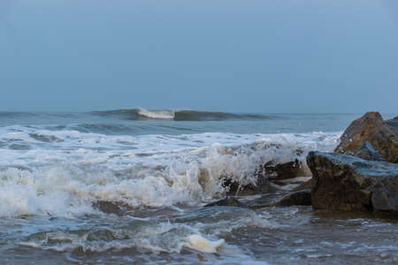 Panoramic landscape view of foamy sea waves from Arabian Sea crashing on the rocks of Gokarna Main Beach or Middle Beach on the West Coast in Gokarna, Uttara Kannada district, Karnataka, India