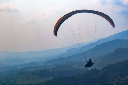 parachute jump: Paragliding on tea garden Stock Photo