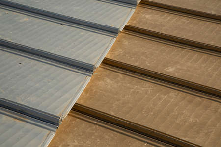 Metallic aluminum sheets in steel and gold color on the roof. close-up
